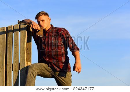 lumberjack guy with ax on blue sky background, camping. lumberjack man with axe in sunset, copy space