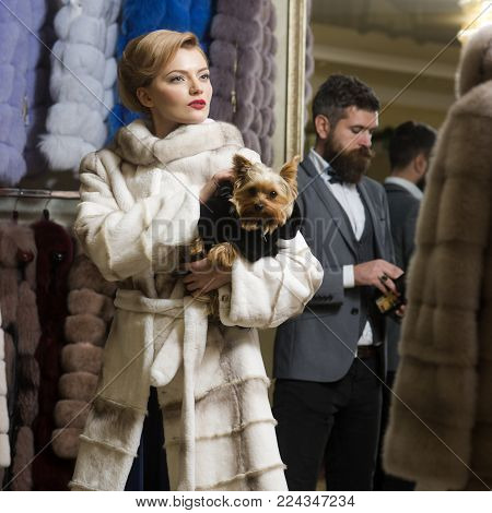 Purchase, business, moneybags. Couple in love among fur coat with dog, luxury. Fashion and beauty, winter. Date, couple, love, man and woman. Woman in fur coat with man, shopping, seller and customer.