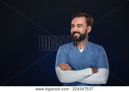 Portrait of a happy male doctor dressed in uniform standing with arms folded and looking away at copy space isolated over dark background