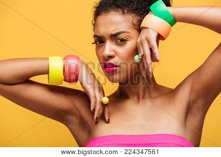 Beauty portrait of beautiful afro american woman with colorful cosmetics and jewelry on hands posing with meaningful look isolated over yellow wall