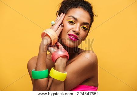 Fashion portrait of beautiful african american woman with bright makeup demonstrating multicolour jewelry holding hands at face isolated over yellow