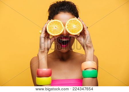 Portrait of amusing afro american woman with fashion accessories having fun and covering eyes with two halves of orange isolated over yellow background