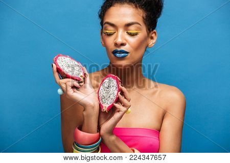 Colorful photo of pretty mixed-race woman with bright cosmetics on face holding ripe pitahaya cut in half in both hands isolated over blue background