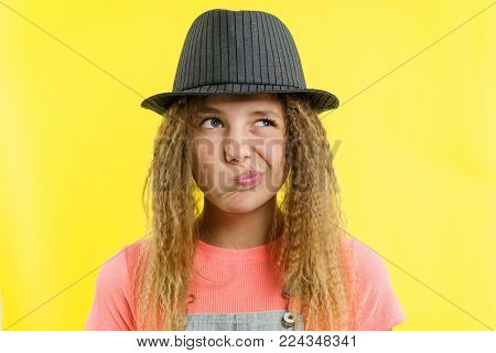 Pretty girl 12-13 years old blonde with curly hair in a hat, looks pensively aside, thinking about school. Facial expressions concept, yellow background
