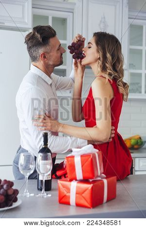 Portrait of a loving romantic smart dressed couple eating grapes while celebrating Valentine's Day on a kitchen at home