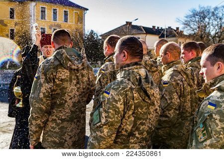 Uzhgorod, Ukraine - January 30, 2018: The priest blesses the soldiers of the 128th separate mountain infantry brigade during their solemn meeting from the ATO zone.