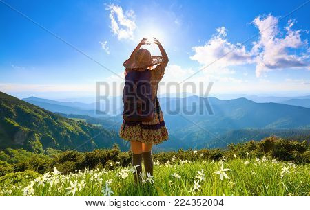 The lawn with white daffodils in the high mountains landscapes. The girl in overknees stockings, romantic dress, back sack and straw hat. A place to relax in the Carpathian Park.