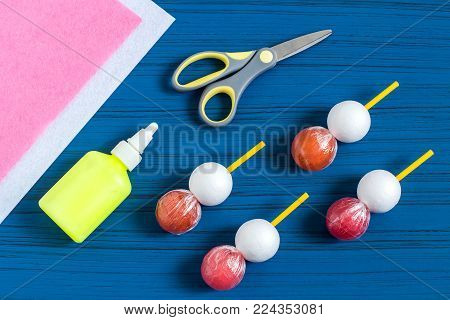 Making Easter bunny from lollipop. Sweet gift to children. Creative idea for children's party. DIY concept. Step by step photo instructions. Step 2. Put styrofoam ball on lollipop