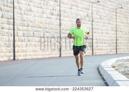 Focused athletic young Caucasian man running down road. Sportsman burning fat and keeping fit on vacation. Sport and fitness concept