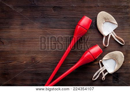 Equipment for rhythmic gymnastics. Clubs and gymnastics shoes on dark wooden background top view. poster