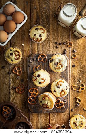 Chocolate chip and pretzel muffins with milk on wooden background for dessert overhead shot