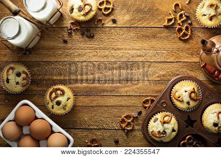 Chocolate chip and pretzel muffins with milk on wooden background for dessert overhead shot with copy space