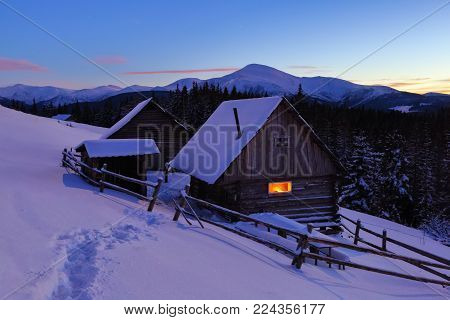 A trodden path leads to the wooden house in the snow on the background of beautiful snow-capped mountains. Fantastic winter scenery.
