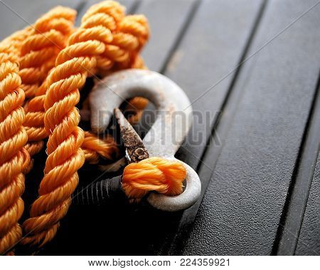 Orange nylon braided rope with metal tow hook. poster