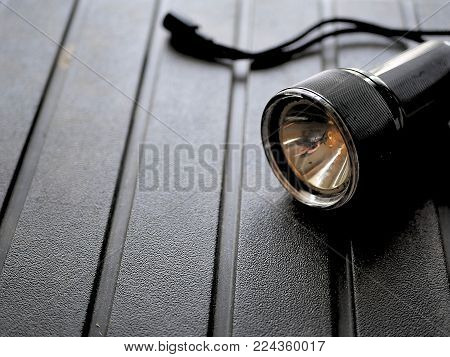 Black safety camping flashlight on rugged background.