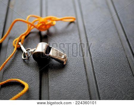 Shiny metal whistle with bright orange lanyard.