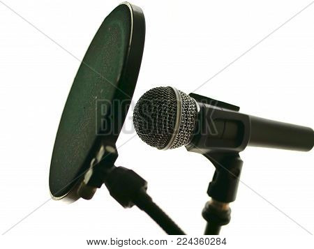 Microphone in recording studio for music, vocals, with pop filter.