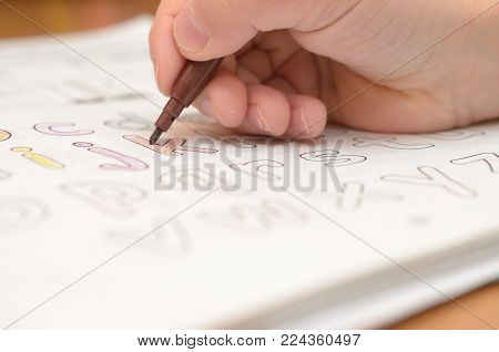 A child's hand writes and displays English letters in a notebook and alphabet with a pencil and felt-tip pen