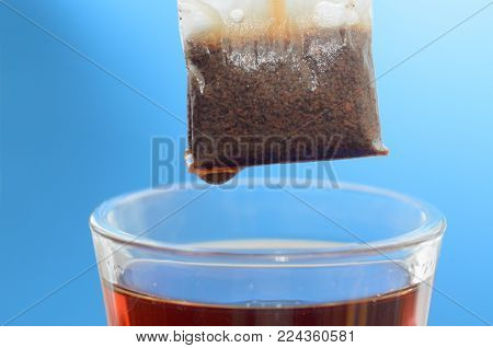 A tea bag over a glass mug with hot water close-up on a blue background