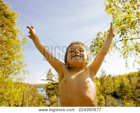 little cute real boy among tree hight, outdoor lifestyle people concept close up