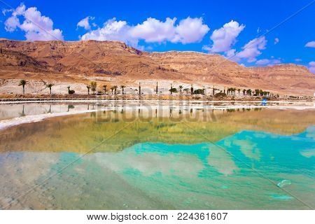 Living Water of the Dead Sea, Israel. Midday heat evaporates water. Between the sea and dry mountains of red sandstone highway passes. The concept of medical and ecological tourism