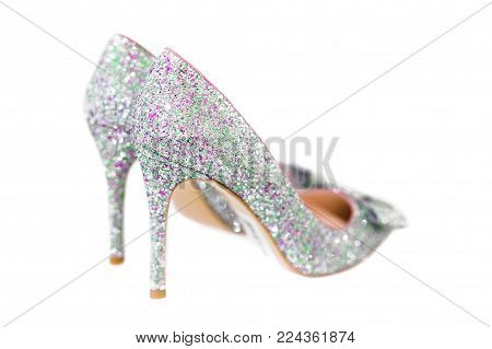 Beautiful silver glitter high heel female shoes isolated on white. Wedding accessories. Cinderella shoes. Selective focus.