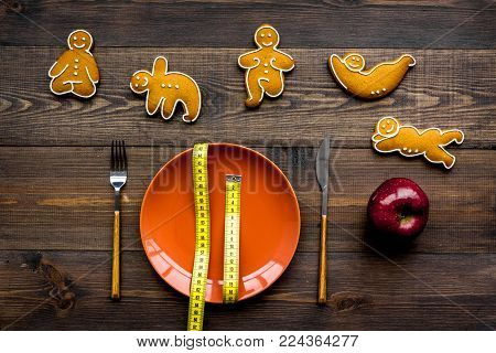 Yoga and healthy diet for lose weight. Plate and cookies in shape of yoga asans on dark wooden background top view.