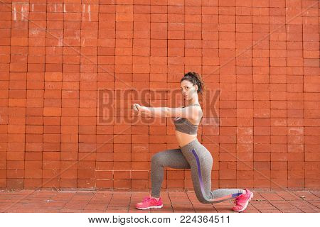 Focused sporty Caucasian girl doing lunges with brick wall in background. Young woman keeping fit and active lifestyle. Sport and fitness concept