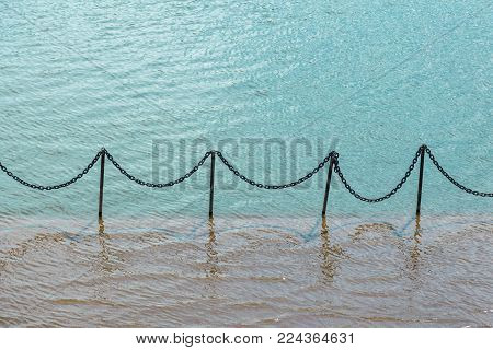 elements of the fence on the flooded pier. black metal bars with chains between them.