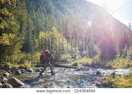 Hiker with backpack crossing mountain river. Hiking river crossing on the stones