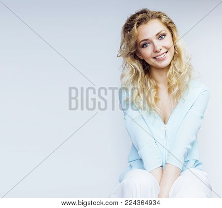 young pretty stylish blond hipster girl posing emotional isolated on white background happy smiling cool smile, lifestyle people concept close up