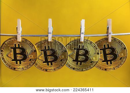 Bitcoin. several coins of bitcoin on a yellow background, Hanging on clothespins