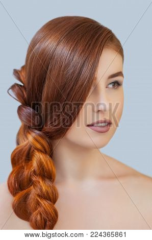 Beautiful girl with long red hair, braided with a French braid, in a beauty salon. Professional hair care and creating hairstyles.