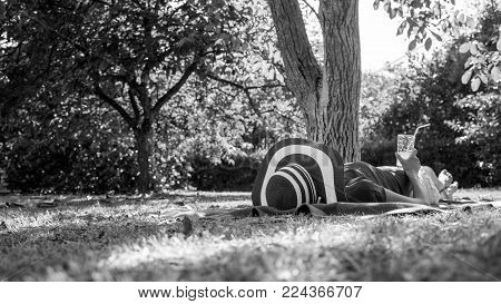 Monochrome image of a woman relaxing in the garden in the shade of a leafy tree lying on a rug on the grass in her sunhat with a refreshing drink.