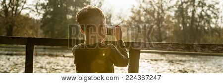 Little boy photographing nature standing in front of wooden railings overlooking a lake or river in a panorama rear view with sun flare.