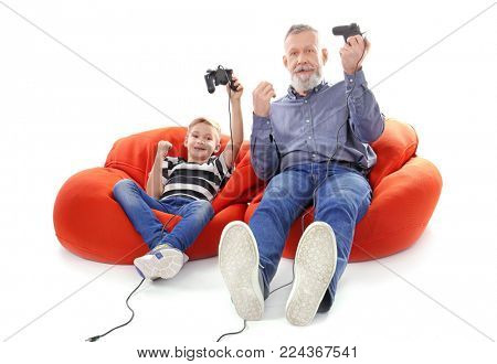 Happy boy and his grandfather with video game controllers on white background