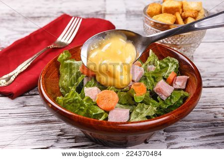 Putting dressing on spoon. Close up of a delicious salad with honey mustard dressing.