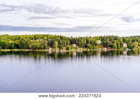 Beautiful panoramic aerial view of Stockholm archipelago, Sweden. Cozy little houses and green nature. Skyline with scenery beyond the village. Summer day with clouds and deep water with reflection