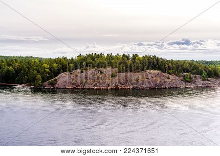Rocky archipelago near Stockholm with vivid green nature on it. Stone island with green pine-trees. Deep blue water around and cloudy sky.