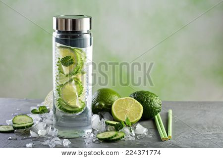Infused water with lime and cucumber in a glass bottle