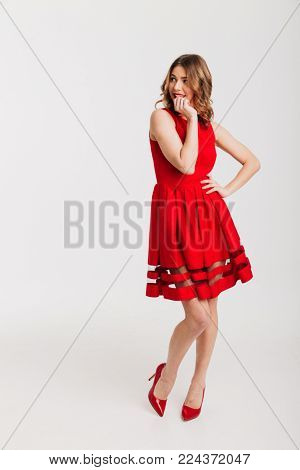 Full length portrait of a lovely petty girl dressed in red dress posing while standing and looking away at copy space isolated over white background