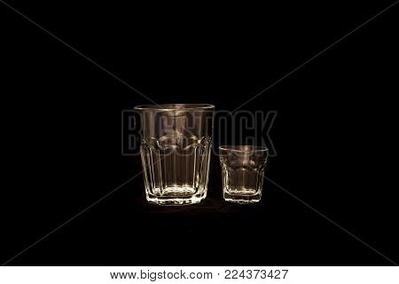 Empty shot glass with simple glass isolated on black background. Two glasses side by side