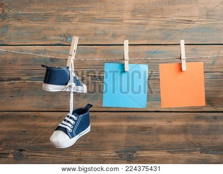 Baby shoes hanging on the colorful clothesline over wooden background