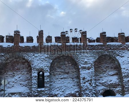 Ancient fortress wall in the winter. The snowy part of the fortress wall of Smolensk. In the foreground close-up is a piece of the wall, on the background of the Ferris wheel and a gray overcast sky.