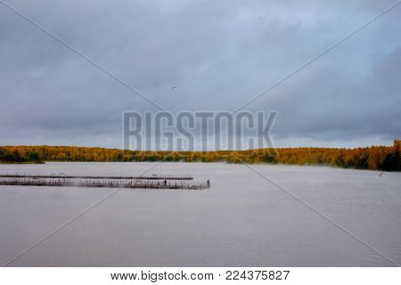 A view of the river with a pier in the fall. Beautiful views of autumn landscape - the river, the fog creeps along the river, fishermen are on the pier, around the autumn trees.