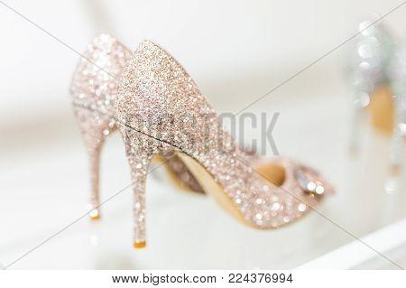 Beautiful golden glitter high heel female shoes on   glass shelf. Wedding accessories. Cinderella shoes. Selective focus.