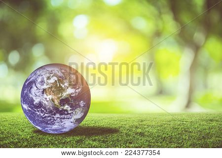 Planet earth beautiful on green grass with nature blur bokeh background, world with conservation and resource for renewable, environment concept, Elements of this image furnished by NASA.