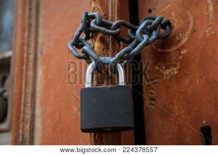 Padlock with chain forbidden the entrance. Wooden brown peeled doorway for backdrop. Closeup, detail