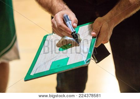 Basketball coach with clipboard and marker explain with scheme the strategy of the game to a player.