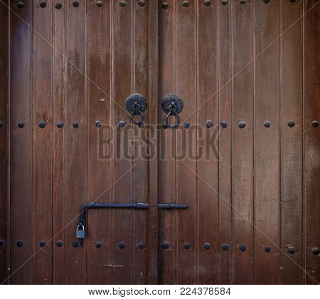Wooden brown door, backdrop with latch and padlock, close up, details
